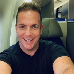 Happy smiley on the plane travel selfie of Ross Johnson